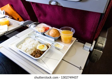 Basic in-flight meal of economy class consisting rice, egg, beef curry, bread, fruits, and juice.