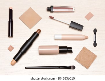 Basic makeup products: primer, concealer, liquid foundation, cosmetic face powder on light wood table, flat lay