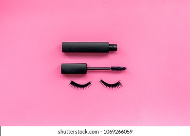 Basic products for eyelashes makeup. Mascara and false eyelashes on pink background top view copy space