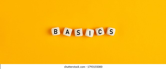 Basics word written on wood blocks on yellow background with flat lay view. Back to basics or simplifying business concept.