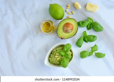 Basil avocado pesto sauce with main ingredients: fresh basil leaves, avocado, parmesan cheese, pine nuts, garlic and lime