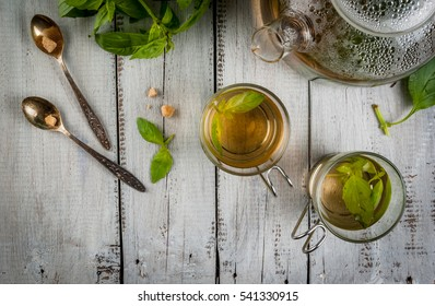 Basil herbal tea in a transparent cup and teapot, spoon with cane sugar, a bunch of fresh basil. On a white wooden table. Copy space top view