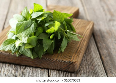 Basil leaves on cutting board grey wooden background