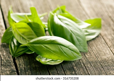 basil leaves on old wooden background