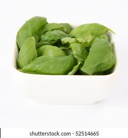 Basil leaves in a small white bowl