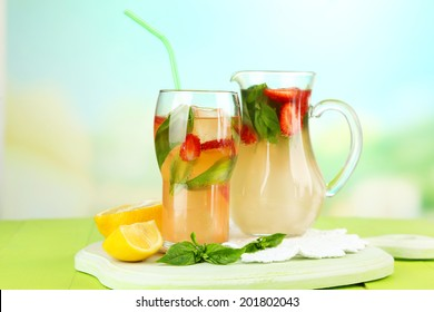 Basil lemonade with strawberry in  jug and glass, on wooden table, on bright background