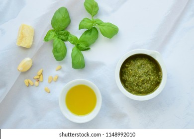 Basil pesto sauce with main ingredients: fresh basil leaves, parmesan cheese, pine nuts, garlic and lime