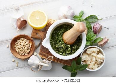 Basil pesto sauce with main ingredients: fresh basil leaves, parmesan cheese, pine nuts, garlic and lemon