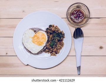 Basil pork and rice and fried egg with chili sauce on wooden table.