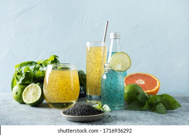 Basil seeds beverage with orange and tropical juice in glasses on light background. Close up. Healthy detox cocktail for lose weight.