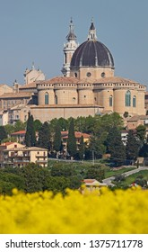 The basilica of the holy house or santuario della santa casa in Loreto province of Ancona in Le Marche Italy with a field of yellow flowers a place of pilgrimage for Catholics and twinned with Lourdes