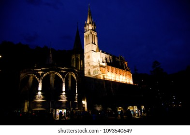 Basilica at night or evening in Lourdes during the candle ceremony or procession.