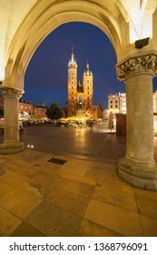 Basilica of Saint Mary at night framed by arch of the Cloth Hall arcade in Krakow, Poland, Gothic church at main square in the Old Town