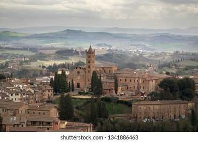 The Basilica of San Clement in Santa Maria dei Servi surrounded by the Tuscan landscapei, Siena, Italy.