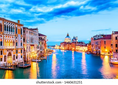 Basilica Santa Maria della Salute, Punta della Dogona and Grand Canal at blue hour sunset in Venice, Italy with boats and reflections.