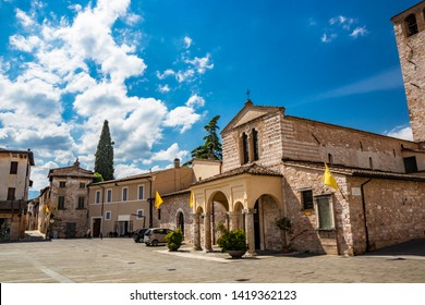 The Basilica of Santa Maria Infraportas, an ancient medieval church, with its tower. The yellow flag of one of the districts. In Foligno, Perugia, Umbria, Italy.