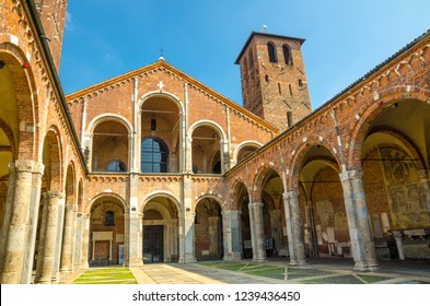 Basilica of Sant'Ambrogio church brick building with bell towers, courtyard, arches, blue sky background, Milan, Lombardy, Italy