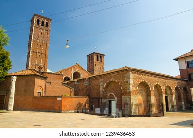 Basilica of Sant'Ambrogio church brick building with bell towers and The Devil's column on square, Milan, Lombardy, Italy