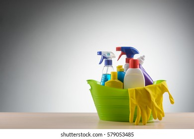 Basin with detergents: rubber gloves, glass and window foaming sprays, liquid detergents, a toilet washing gel and a bleach. Standing on the light table, blank backround, place to insert your text.