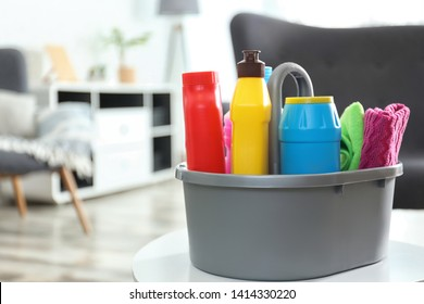 Basin with different detergents on table indoors, space for text. Cleaning service