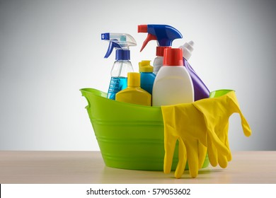 Basin with latex gloves and detergents: glass and surface cleaning sprays, a stain remover, a bleach, a toilet cleaning liquid, a dishwashing liquid. Standing on a wooden table, neutral background.
