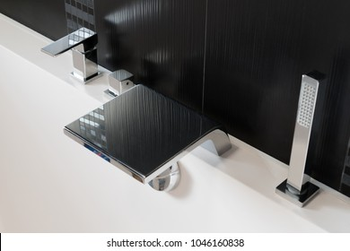Basin mixer tap, bath shower mixer, waterfall faucet and shower head on the side of the bathtub close-up. rectangular modern design in black and white.