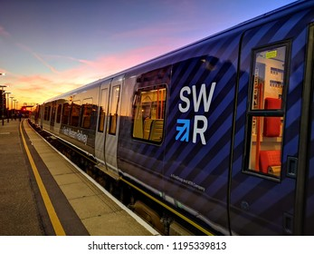 Basingstoke, UK. 24th September 2018.  A newly liveried South Western Railway Class 450 Desiro train is in the platform at Basingstoke Station just before sundown.