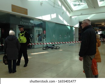 Basingstoke, UK- February 25, 2019: a police officer talking to potential witnesses after a smash and grab robbery at Beverbrook's jewellery shop in Festival Place, basingstoke
