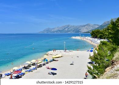 Baska Voda, Croatia, 15 June, 2019: Adriatic sea beach in Baska Voda with mountain view. Blue flag Nikolina beach.