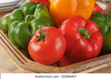 A basked of peppers, tomatoes and vegetables