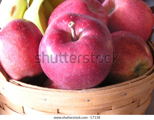 A basket of apples with a hint of bananas in the background.