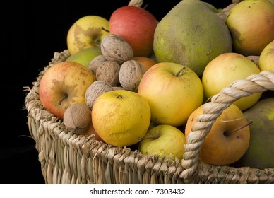 a basket with apples, nuts, quinces