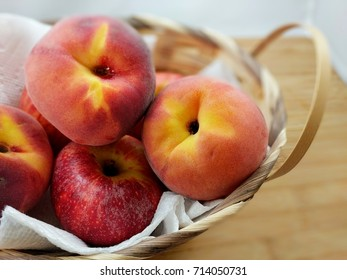 basket of apples and peaches on wooden cutting board