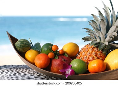 Basket of assorted tropical fruits and flowers, sea on the background