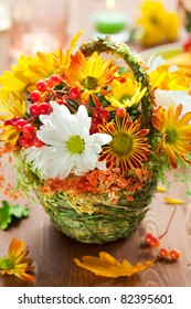 basket of autumn flowers on the wooden table