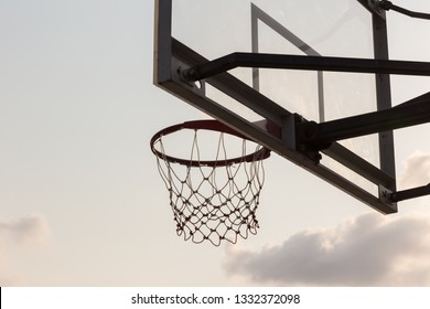 basket ball board under sky with white clouds. Basketball court with old backboard. sky and white clouds on background. Old basket ball Stadium.  basketball hoop in sky background on evening.