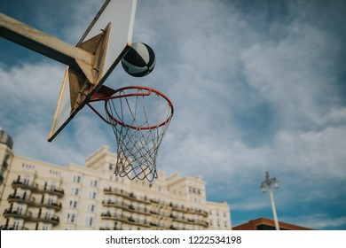 Basket ball entering into a basketball ring, at an urban court, with blue sky background.
