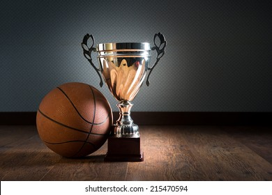 Basket ball and gold bright trophy on hardwood floor.