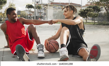 basket ball players sitting and relaxing on court having a conversation after a game. concept of diversity and multi ethnic people in  sports team.