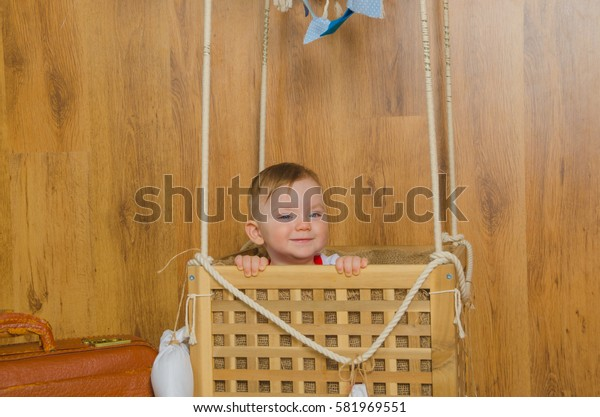 in the basket of the balloon, playing a boy child