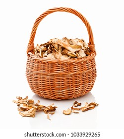 Basket basketful of dried mushrooms. Rounded wattled basket full of dried edibles, isolated on white background with shadow reflection. Darning-eggs in wooden pannier. Ceps in skep. Domes in pannier