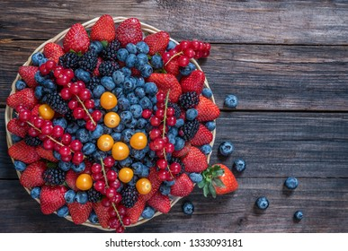 Basket with berries strawberries, blueberries, blackberries and red currants on a wooden surface. Top view.Copy space