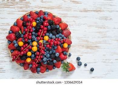 Basket with berries strawberries, blueberries, blackberries and red currants on a white wooden surface. Top view.Copy space.