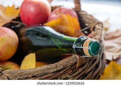a basket with bottle of cider and delicious apples, autumn leaves