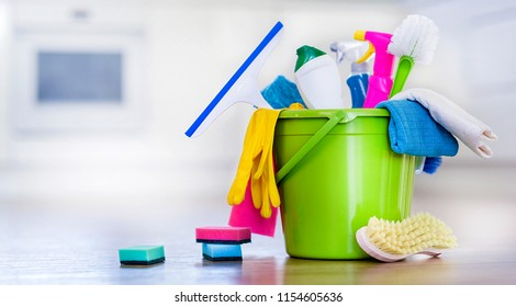 Basket or bucket with cleaning items on blurry modern kitchen background. Washing set colorful with copy space.