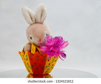 A basket with bunny and purple feather flower on white background