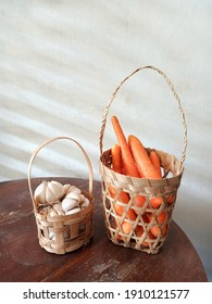 A basket of carrots and small basket of garlic on a wooden table
