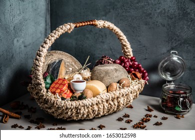Basket with cheese, honey and grapes on a blue background