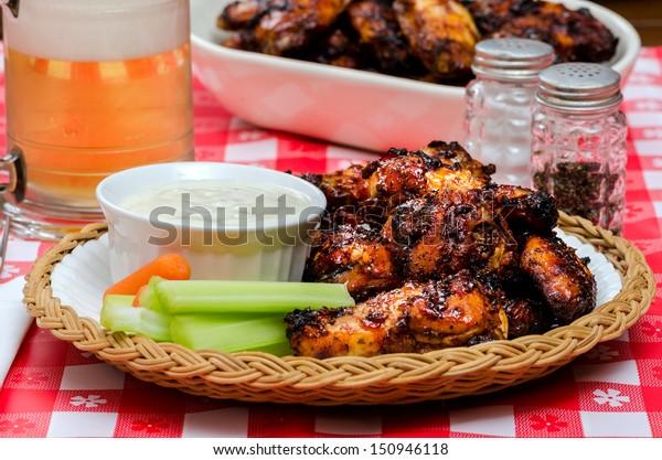 Basket of chicken wings with dip, celery,carrots & beer