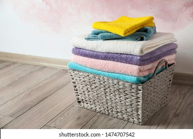 Basket with clean laundry on wooden floor near pink wall, space for text